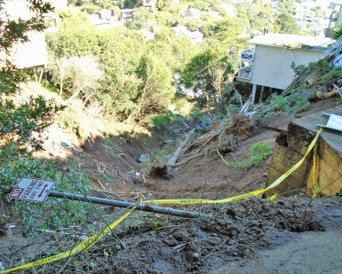 A view looking downhill of the damage from a mudslide in Sausalito, with a wrecked home at the bottom of the hill.