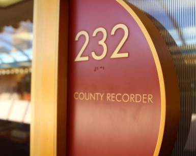 A closeup view of the sign outside the door of Suite 232 that says County Recorder