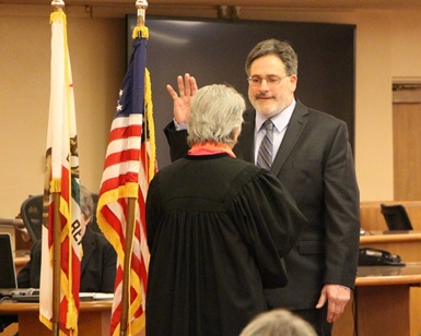 Dennis Rodoni raises his right hand and takes the oath of office from Judge Faye D'Opal.