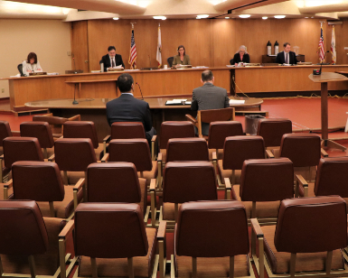 A view of the March 24 Board of Supervisors meeting ,showing mostly empty seats in the foreground and the Board members sitting further apart from usual at the dais.