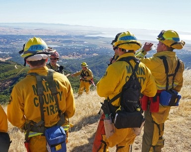 Several firefighter trainees in their 20s, wearing fireproof turnout gear, stand atop a hill overlooking San Francisco Bay during a pause in training.