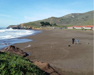 A man and woman walk their dog on Rodeo Beach in the Marin Headlands.