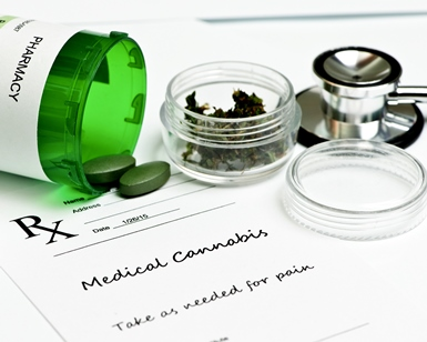 Tablets of medical cannabis on a table with a small container of leaves and a stethoscope