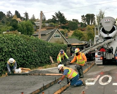 Construction workers flow wet concrete out of a cement mixer truck and onto a sidewalk.
