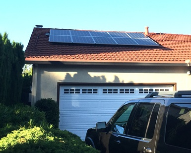 A roof above a home's garage has solar panels on it.