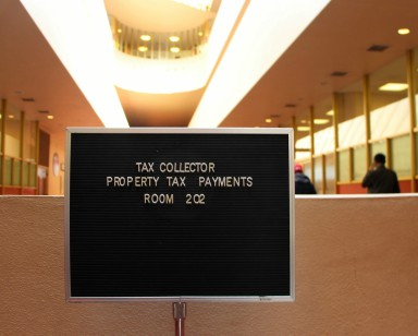 A sign in the Civic Center lobby shows that property taxes can be dropped off in Suite 202.