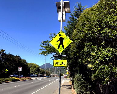 A new pedestrian safety crosswalk beacon installed on a sign adjacent to a busy road.