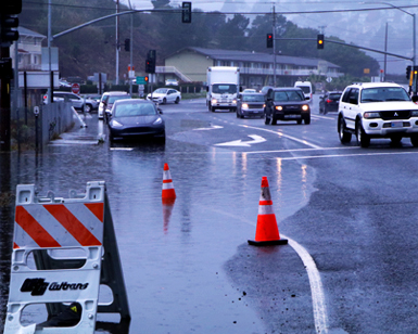 A view of flooded roadway and vehicles moving around puddles at the entrance of the Manzanita Park & Ride lot near Sausalito.