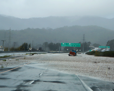 A road-level view of Highway 37 during recent flooding, with a truck stuck in the water in the distance.