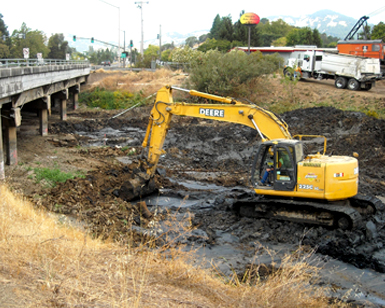 A heavy equipment operator uses an excavator to dredge Novato Creek.