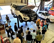 About a dozen teen students look at the underside of an SUV up on a hydraulic lift inside the County Garage as a mechanic describes the fleet maintenance program.