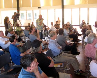 A man speaks with a microphone in front of a group of people attending a flood control meeting.