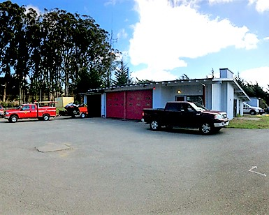 An exterior view of the Tomales Fire Station with several trucks out front.