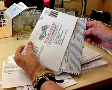A close-up view of two hands holding a ballot envelope and one of the hands pulling out the ballot.