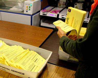 An election worker thumbs through mailed ballots on Election Day at the Civic Center.