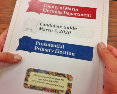A closeup view of a person's hands holding a candidate guidebook for the March 2020 election.