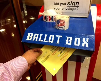 A man's hand holds a voter ballot as he puts it into a ballot box.