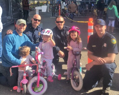 Four firefighters pose with three young girls who received new bikes in Santa Rosa.