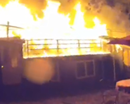 A Screenshot of the Fairfax house fire of July 14, 2019 Image taken from video footage of the response.  Image shows single story home with rooftop deck and patio table in yard.  House is on fire.