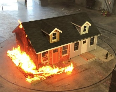 A tabletop model of a typical single-family home shows how fire resistant materials don't burn and traditional materials burn.
