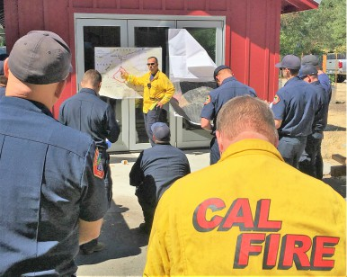 Fire Incident Commander Mark Brown provides a briefing to a group of firefighters.