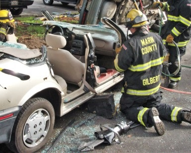 "Three firefighters work on a mangled car during an extrication drill as a ""jaws of life"" device sits on the pavement in the foreground."