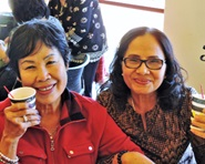 Two smiling senior women hold up their coffee cups.
