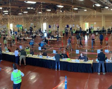 An interior view of the vaccination operation inside Exhibit Hall on the Marin Center campus showing dozens of people spread out in the large room.