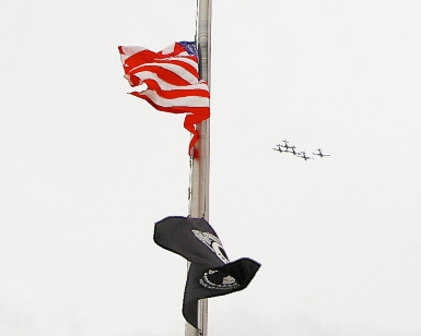 A view of a flagpole with an American flag at half staff and a POW MIA flag below it, with five antique airplanes flying in the distance.