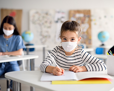 Two female students sit at desks in a classroom, where the desks are spaced more than 6 feet apart and the students are wearing masks.