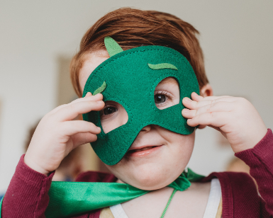 A young smiling boy adjusts his homemade green felt mask