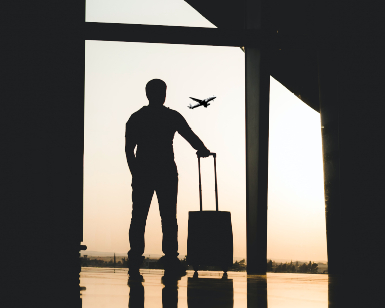 A photo shows a silhouette of a male traveler with a suitcase standing in an airport lounge and looking through a window at an airplane taking off.