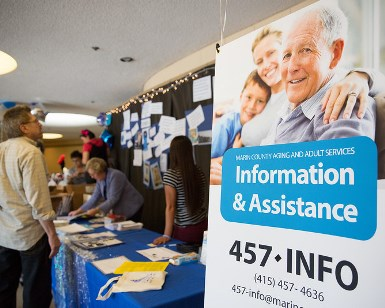 On the right is a 5-foot-tall sign promoting the Information & Assistance phone number 415-457-INFO. On the left are people mingling at an information table at senior fair.