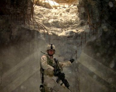 Tom Tarantino is shown in full combat gear in a blown out bunker in the Middle East during one of his deployments.