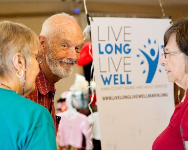 An older man smiles at the camera next to a sign that says Live Long Live Well.