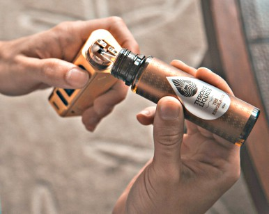 Two hands are shown with a vaping product.