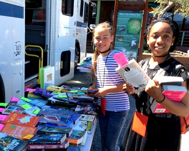 Two pre-teen girls pick out books at the Bookmobile.