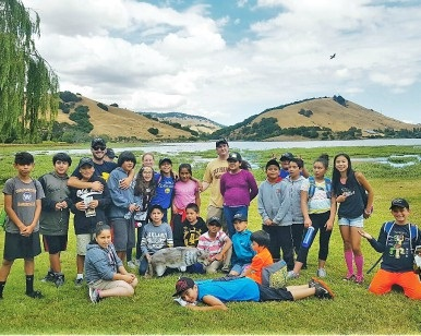 About a dozen elementary school and middle school kids on a lawn at Stafford Lake Park in Novato.