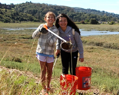 Two young girls show off some garbage that they picked up during a Coastal Cleanup Day