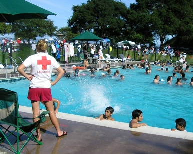A female lifeguard stands watch next to the McNears Beach Park pool as kids play in the water.