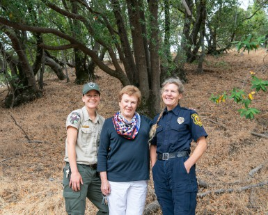 A female park ranger, a female resident and a female firefighter pose and smile in a wooded area of Pacheco Valle.