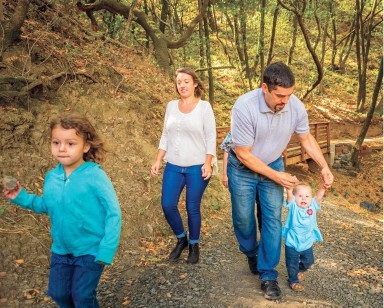 A husband and wife walk on a trail with their two young kids.
