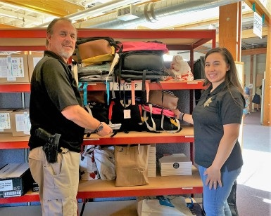 Deputy Probation Officer Mark Messner and Probation Officer Brenda Godoy stand next to shelves with backpacks and other school supplies.
