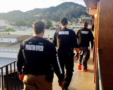 Three Probation officers walk on an apartment balcony during a DUI compliance check.