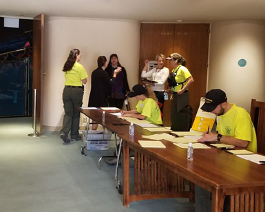 Seven people are shown preparing for fire evacuees in the lobby of the Veterans Memorial Auditorium at Marin Center.