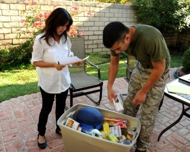 A man and a woman go through a plastic bin full of emergency supplies