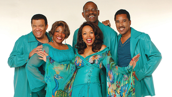 Fifth Dimension singing group posing together in matching teal costumes.