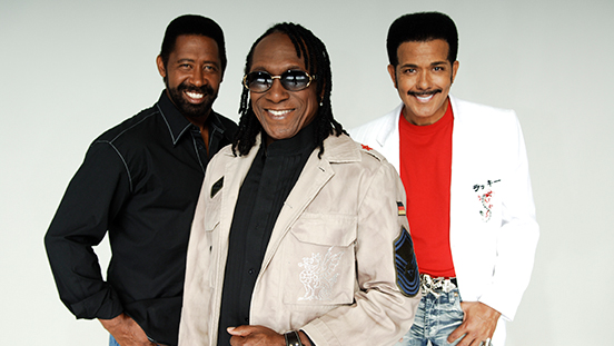 The Commodores singing group posing together.