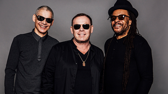 UB40 singing group posing together.