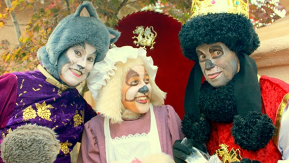 Three actors dressed as characters from Cinderella, portrayed as dogs.